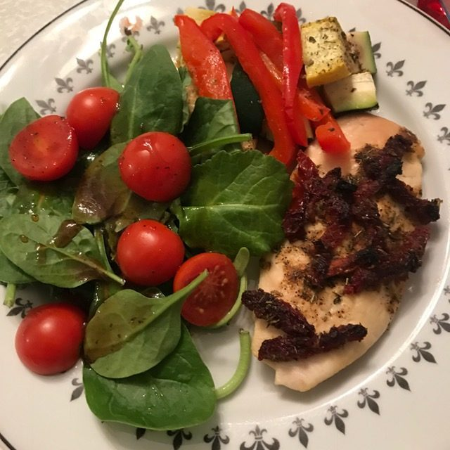 Chicken and veggies on plate with salad